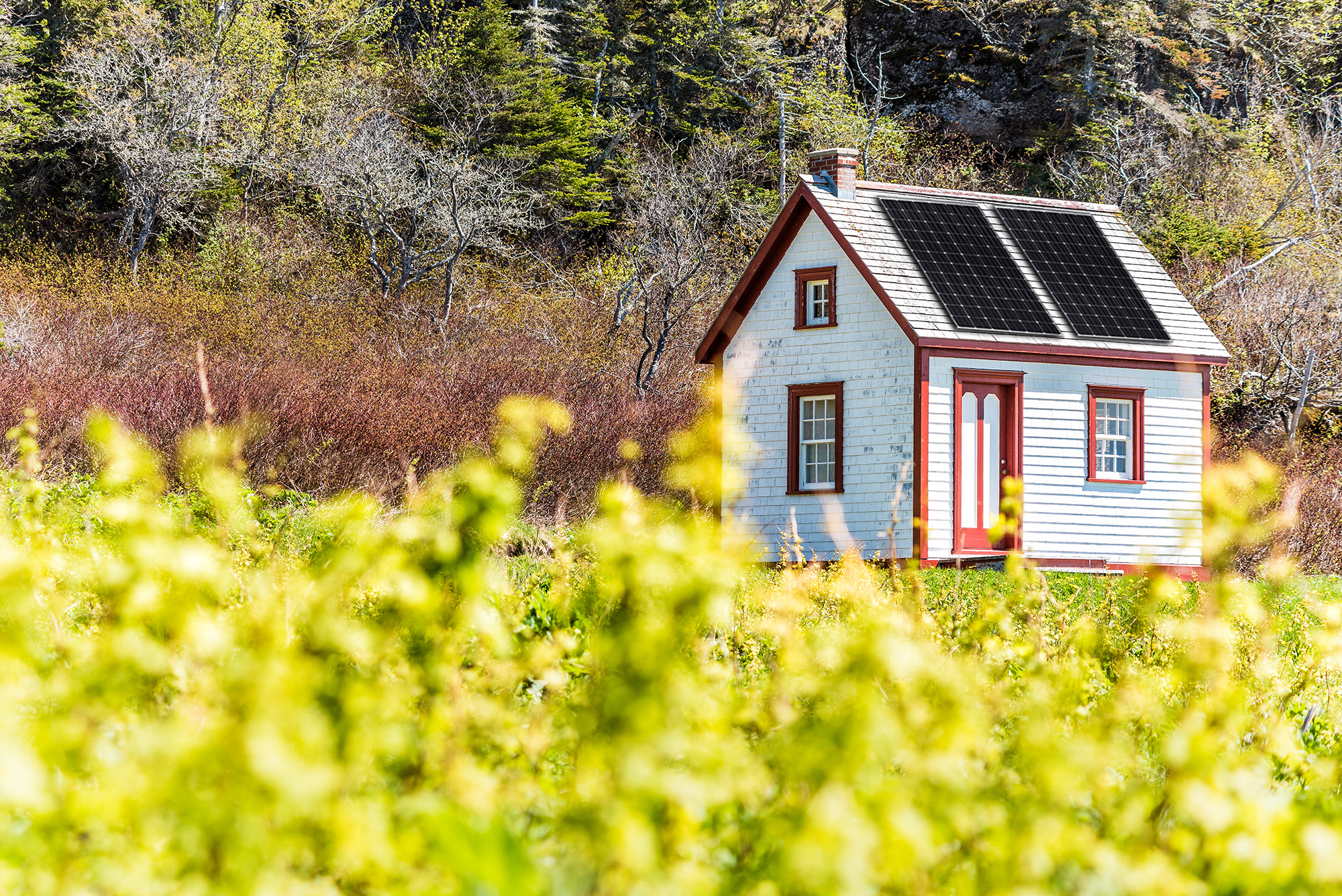 Old vintage white and red wooden tiny house with solar panels on the roof