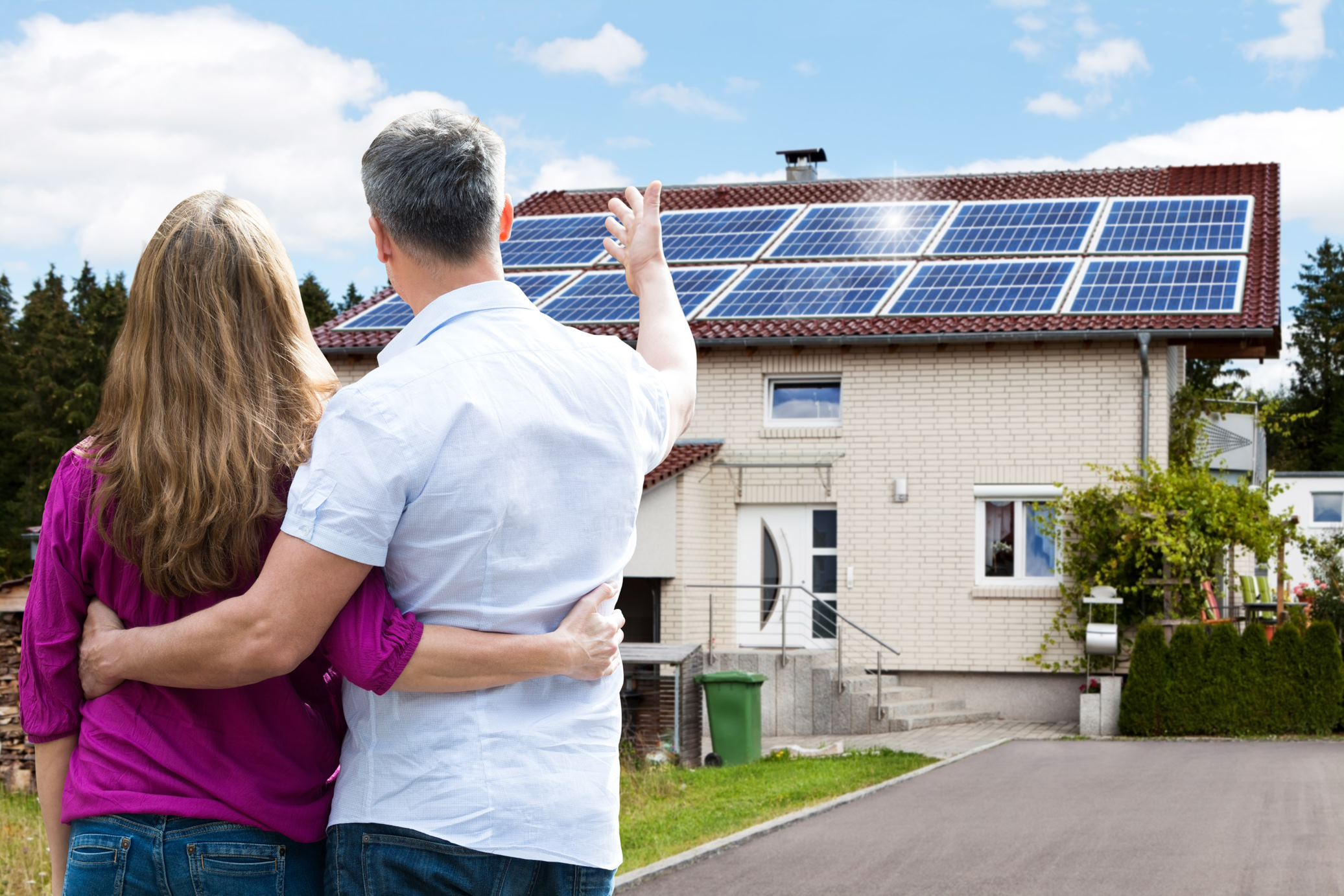 family standing outside of home with solar panels